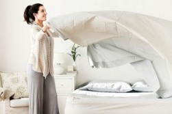 Woman-changing-bedsheets-300x200
